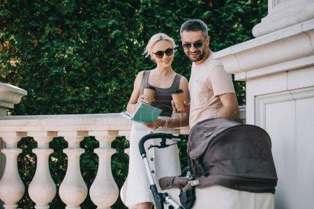 Foto de Padres junto a carro de bebé en el parque y sosteniendo el libro con el café para ir - Imagen libre de derechos