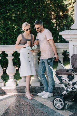 Photo pour Parents, debout près de Landau dans le parc, lecture de livre et tenant des tasses à café jetables - image libre de droit