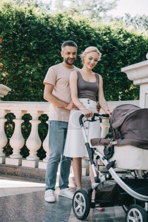 Photo for Husband hugging wife near with baby carriage in park and they looking at kid - Royalty Free Image