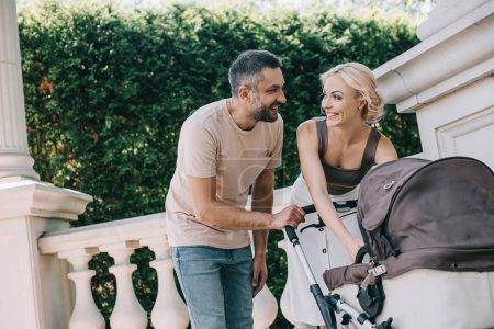 Foto de Padres felices mirando el uno al otro cerca carro de bebé en el Parque - Imagen libre de derechos