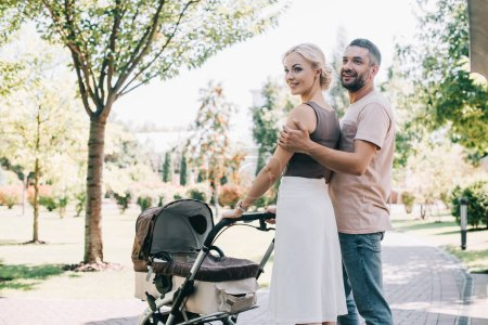 Photo for Happy parents hugging and walking with baby carriage in park - Royalty Free Image