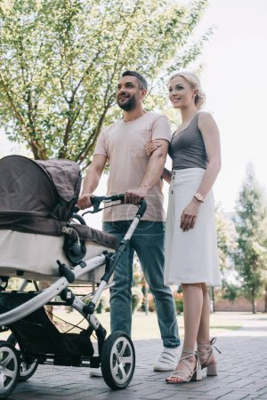 Photo for Low angle view of happy parents walking with baby carriage in park - Royalty Free Image