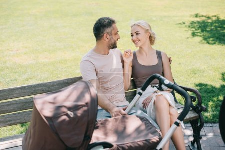 Photo for Smiling parents sitting on bench near baby carriage in park and looking at each other - Royalty Free Image