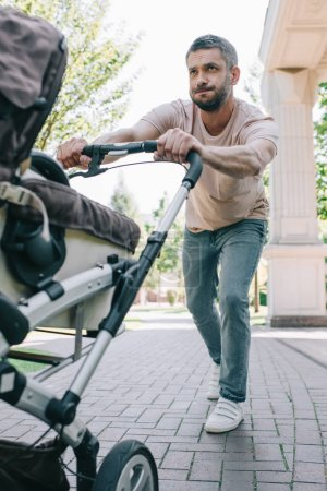 father pushing heavy baby carriage in park