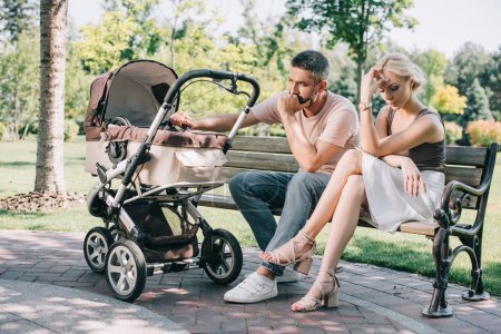sad parents sitting on bench near baby carriage in park