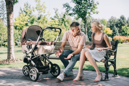 parents quarreling on bench near baby carriage in park