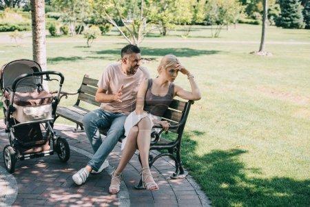 Foto de Marido esposa grita y sentado sobre un banco cerca del carro de bebé en el Parque - Imagen libre de derechos