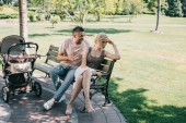 husband yelling at wife and sitting on bench near baby carriage in park