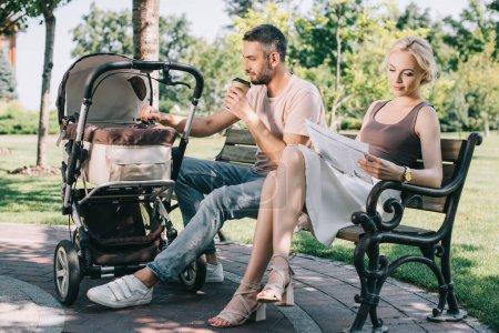 père de boire du café et toucher la poussette dans le parc, mère lisant Journal