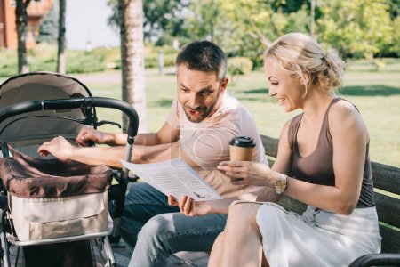 wife showing newspaper to surprised husband on bench near baby carriage in park
