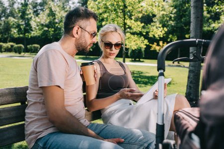 parents sitting on bench near baby carriage and looking at tablet