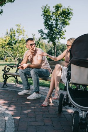 father smoking cigarette near baby carriage in park, angry mother pointing on cigarette