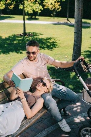 vue d'angle élevé de femme allongée sur les jambes mari près de Landau dans le parc et la tenue de livre