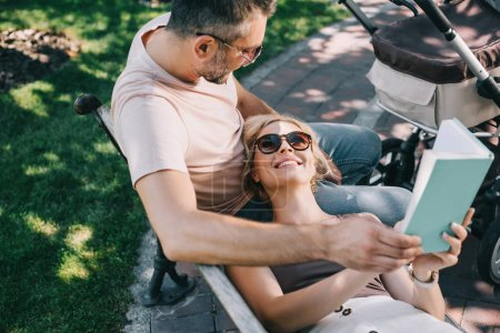 high angle view of smiling wife lying on husband legs near baby carriage in park and holding book