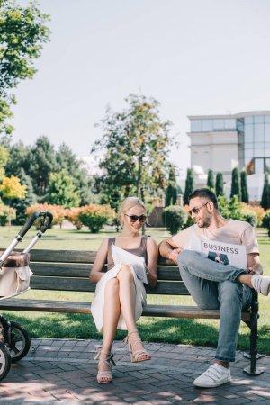 parents, assis sur un banc près de Landau dans le parc et lisant un journal magazine et d'affaires