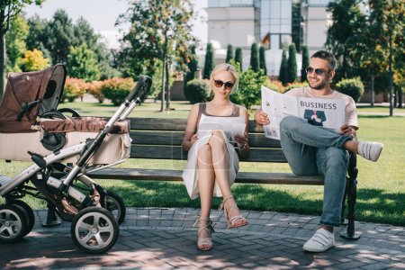 parents sitting on bench near baby carriage in park and reading magazine and newspaper