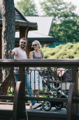 happy parents standing with baby carriage on bridge in park, man pointing on something to woman
