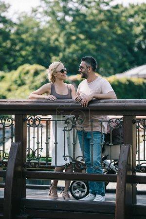 Photo pour Heureux parents debout avec Landau sur le pont dans le parc et regarder les uns les autres - image libre de droit