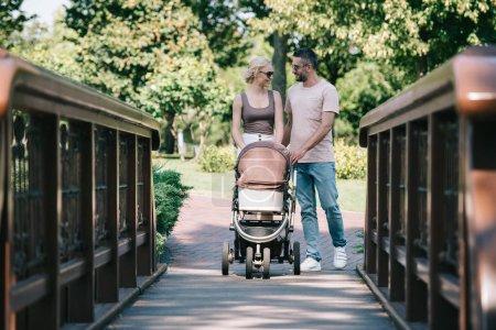 Foto de Padres felices caminando con el carro de bebé en puente en el parque y mirando el uno al otro - Imagen libre de derechos