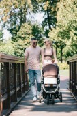 happy parents walking with baby carriage on bridge in park