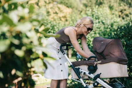 smiling mother touching kid in baby carriage in park