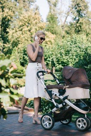 mère en lunettes de soleil marchant avec Landau dans le parc et parler de smartphone