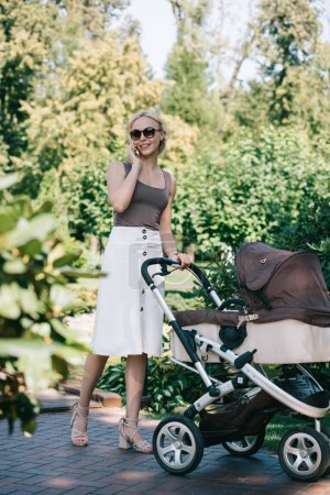 mother walking with baby carriage in park and talking by smartphone