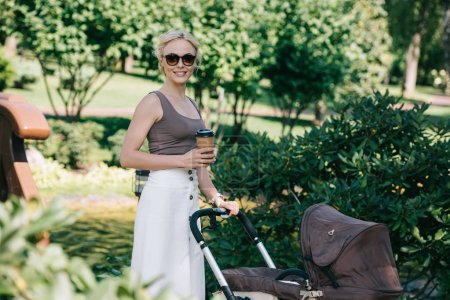 mother walking with baby carriage in park and holding coffee to go