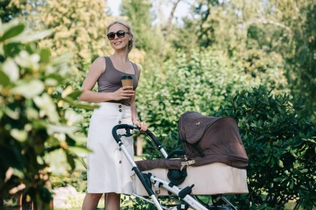 mother walking with baby carriage in park and holding disposable coffee cup