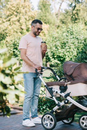 father walking with baby carriage in park and holding disposable coffee cup