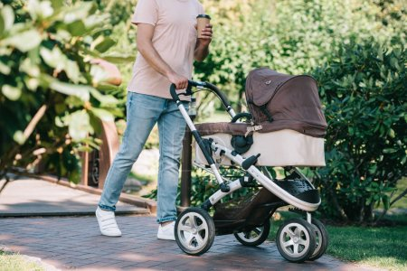 cropped image of father walking with baby carriage and disposable coffee cup in park