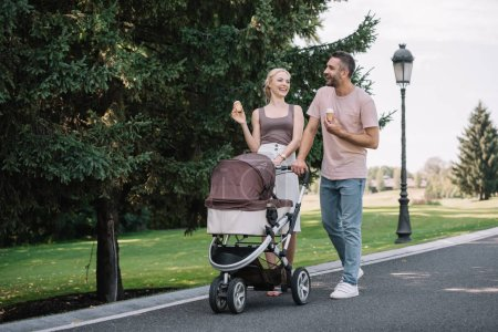 happy parents walking with baby carriage and ice cream in park