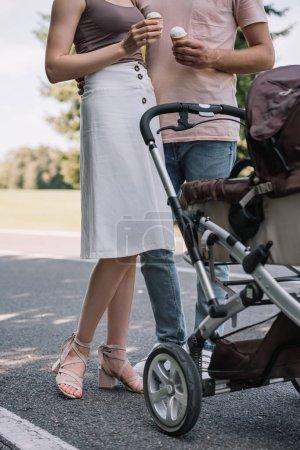 Cropped image de parents tenant glace crème et debout près de Landau dans le parc
