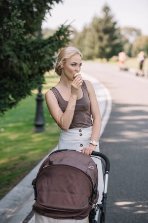 portrait of mother walking with baby carriage and eating ice cream in park