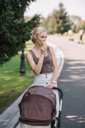Portrait de mère marche avec Landau et manger de la crème glacée dans le parc