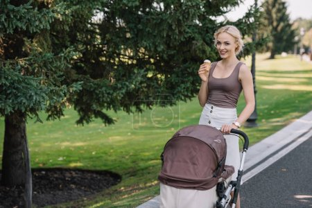smiling mother walking with baby carriage and ice cream in park