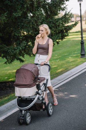 mother walking with baby carriage and eating ice cream in park