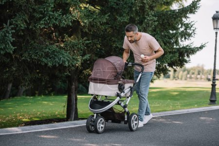 smiling father walking with baby carriage and ice cream in park and looking at baby