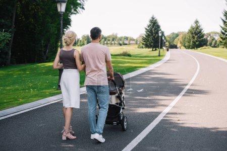 vue arrière du parents marcher avec Landau sur route dans le parc