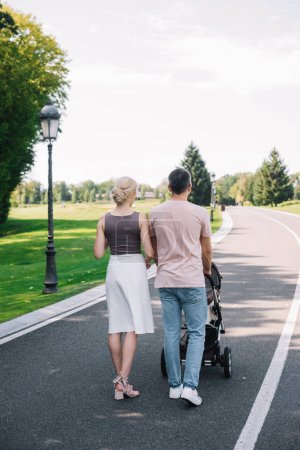 rear view of parents walking with baby carriage on road in park