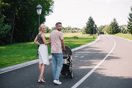 back view of parents walking with baby carriage on road in park and looking at camera