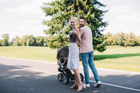 back view of parents walking with baby carriage on road in park, mother waving hand