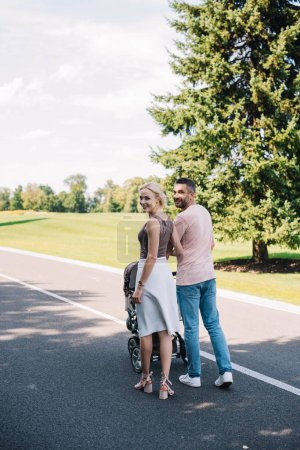 parents walking with baby carriage on road in park and looking at camera