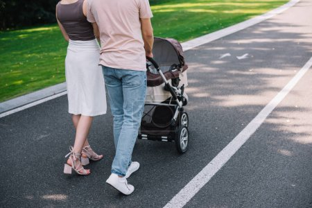 Photo for Cropped image of parents walking with baby carriage on road in park - Royalty Free Image