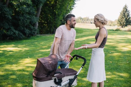 Photo for Side view of parents quarreling near baby carriage in park - Royalty Free Image