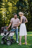 angry parents quarreling near baby carriage in park
