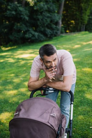 father smoking cigarette near baby carriage in park and looking away