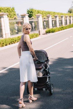 vue arrière du mère irritée marche avec Landau dans le parc
