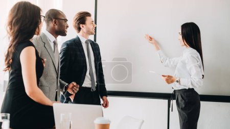 Photo for Multicultural business people looking at empty white board during business meeting in office - Royalty Free Image