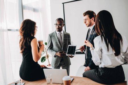 Photo pour Groupe de collaborateurs d'affaires multiraciale dans vêtements discutant le nouveau plan d'affaires au bureau - image libre de droit